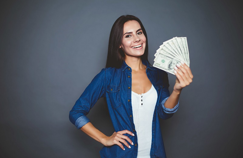 Woman holding money she saved with LASIK